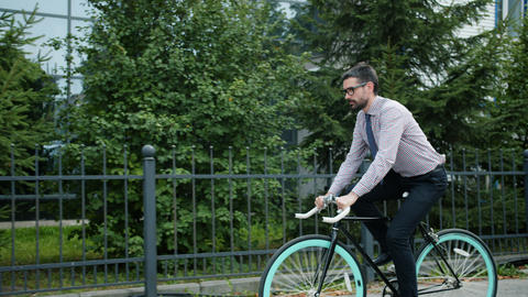 Slow motion of young businessman riding bike outdoors wearing formal clothing Live Action