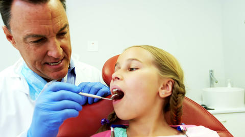 Dentist examining a young patient with tools Live Action