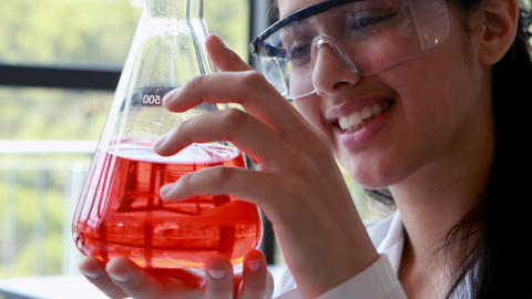Attentive schoolgirl doing a chemical experiment in laboratory Live Action