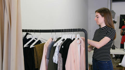 Female stylish selecting apparel from clothes rack Live Action