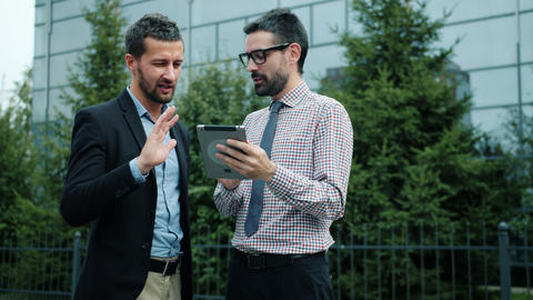 Businessmen with tablet talking using internet outdoors in city street smiling Live Action