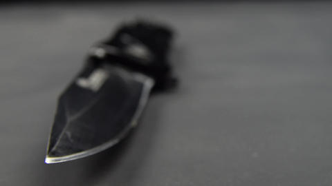Black folding knife on a black table surface. Sharp edge blade Live Action