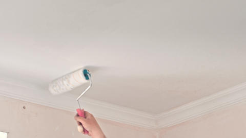 Male Hand Painting Wall with Paint Roller Live Action