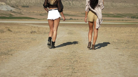 legs of two young slender women walking along a country road in the hot summer Live Action