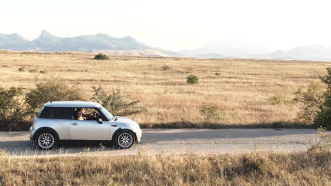 Two young women ride in a car against the backdrop of a mountain range Live Action