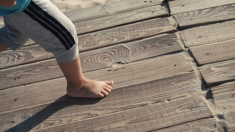 117 boy runs on wooden path Footage