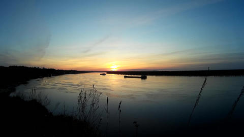 Beautiful sunset on the coast next to the river . The clouds cross the sky Footage
