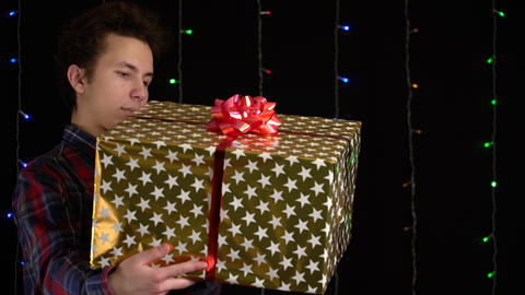 boy with a gift box on black background. gift box with... Stock Video Footage