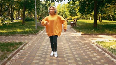 blonde female using headphones dance outdoor Live Action