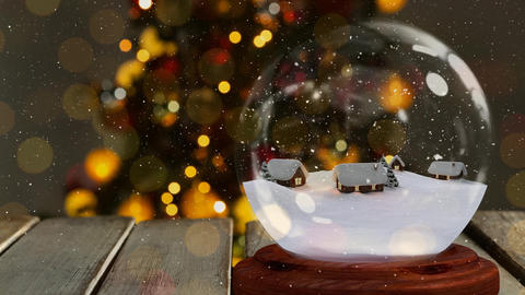 Christmas animation of snow houses in snow globe on wooden table 4k Animation
