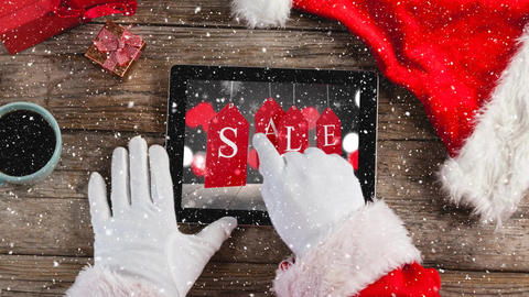 Video composition with snow over desk with santa hand on laptop Animation