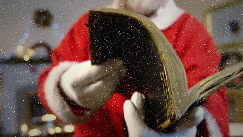Video composition with falling snow over slow motion santa flipping through book Animation
