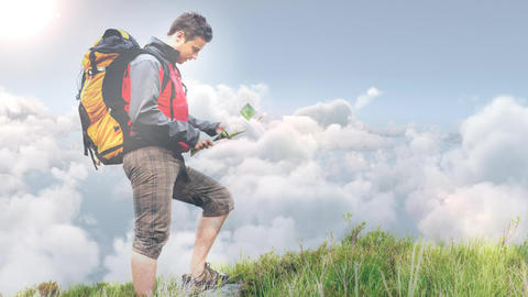 Male Hiker looking at map standing on hill video Animation