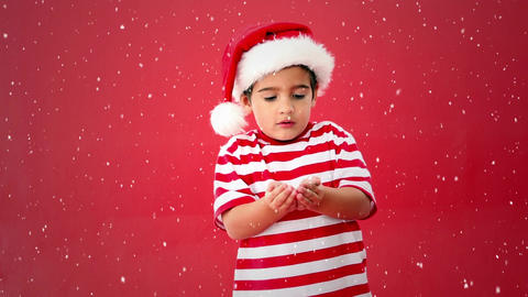 Video composition with falling snow over boy with christmas hat blowing snow Animation