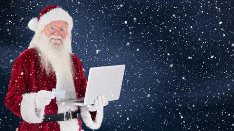 Santa clause holding a laptop combined with falling snow Animation