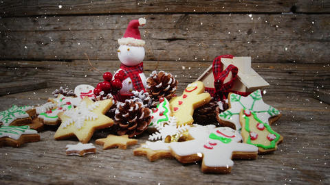 Video composition with falling snow over desk with ginger cookies and santa doll Animation