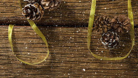 Falling snow with Christmas pine cones decorations on wood Animation