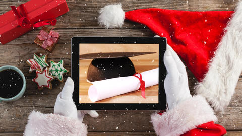 Video composition with snow over of top view of santa holding tablet Animation
