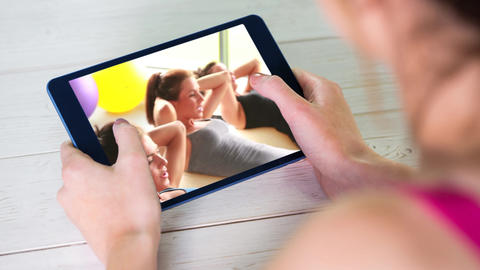 Digital animation of woman watching a video of exercise tutorials on digital tablet 4k Animation