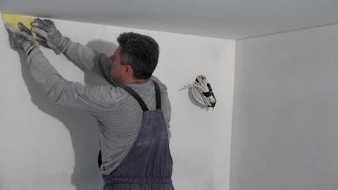 worker with gloves smooth wall surface with sand paper Live Action
