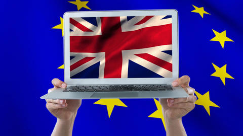 Two hands holding a laptop with the british flag in full screen Animation