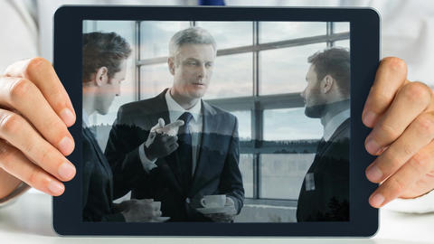Hands holding tablet showing business meeting video Animation