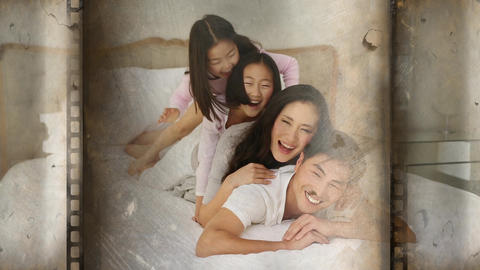 Cheerful family of four lying over each other in bed Animation