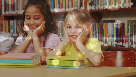 Schoolgirls leaning on a table and looking at the camera with books in front of them in a library Animation