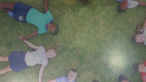 Children lying on the grass holding hands Animation