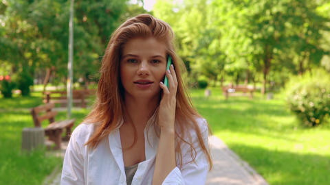 attractive female has phone conversation in park Live Action
