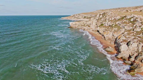 bird eye view of seawaves crashing against an empty beach from above Live Action