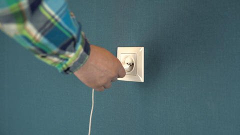 A man plugs a phone charger into a wall outlet. Rosette in the wall with dark Live Action
