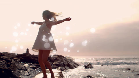 Young woman dancing on the waterside at beach with light effect Animation