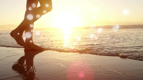 Woman walking barefoot in ocean on the sand against sunshine on ocean Animation