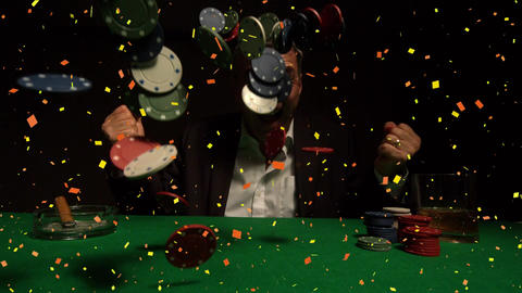 Casino winner sitting at casino table while tokens and confetti falling on table in slow motion Animation