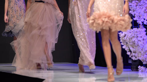 Female models walk the runway in colourful dresses during a Fashion Show. Fashion catwalk event Live Action