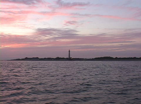 A silhouette of a lighthouse adorns the shoreline during... Stock Video Footage