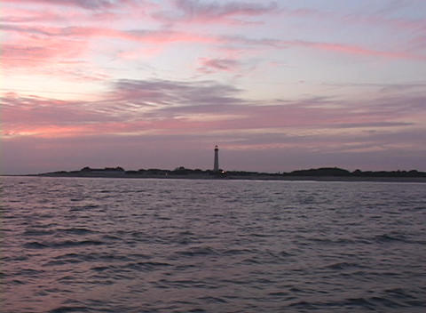 A silhouette of a lighthouse adorns the shoreline during golden-hour Footage