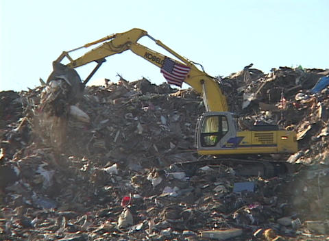 A large scoop shovel dumps debris from Hurricane Katrina Stock Video Footage