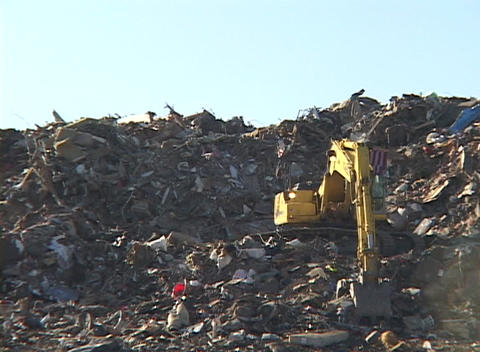 A large scoop shovel dumps debris from Hurricane Katrina Footage