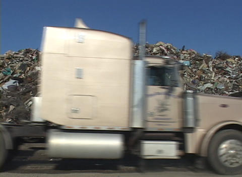 A large dump truck passes by a pile of debris left by Hurricane Katrina Footage