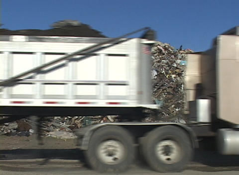 A large dump truck passes by a pile of debris left by... Stock Video Footage