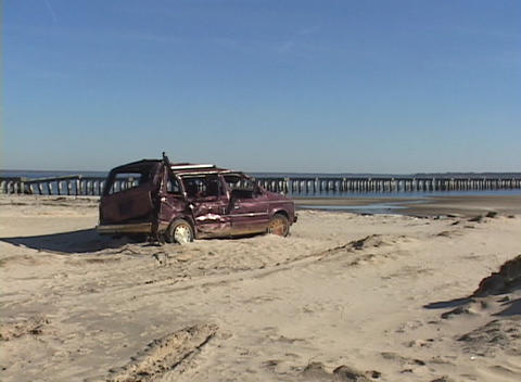 A destroyed minivan abandoned on a beach shows the... Stock Video Footage