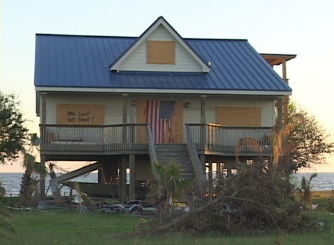 Medium shot of a boarded up house displaying an American flag, abandoned after Hurricane Katrina Footage