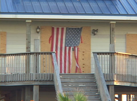 Medium shot of a boarded up house with a torn American flag following Hurricane Katrina Footage