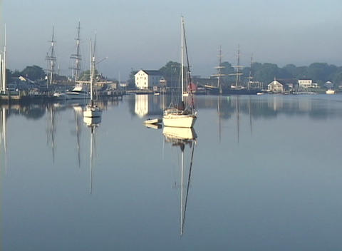Several boats rest in a glass-like harbor Stock Video Footage