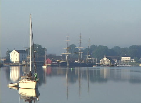 Houses overlook boats resting in a calm harbor Stock Video Footage