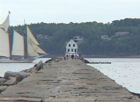 A sail boat passes a jetty Stock Video Footage