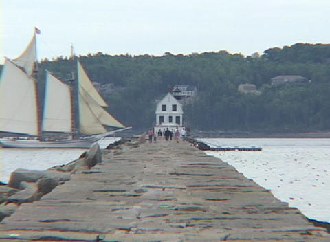 A sail boat passes a jetty Footage