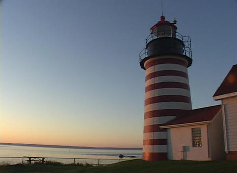 A coastal lighthouse rests next to the ocean Stock Video Footage